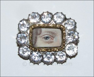 "A lady's blue eye painted in miniature on ivory, set in gold and surrounded by white sapphires. ¾"" x ⅝"" Late 18th century."