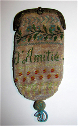 "Figure 1  Very finely knitted beadwork and ball tassel. Design includes the words ""Souvenir d'Amitié"" — a remembrance or memento of friendship. 4"" x 2""."