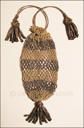 "Figure 1 Small, netted, tubular drawstring purse, with alternating bands of gray silk and silver metallic thread. Drawstrings of woven silver metallic thread are topped with tassels made of very fine silvered wire shaped into tiny coils. Matching tassel at the base of the purse. 4"" long, from drawstring to tassel bead. c1790."
